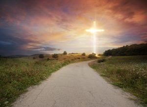 A road leading to a bright cross